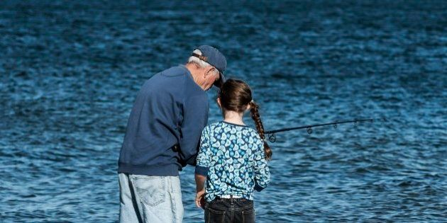 CAPE COD, MASSACHUSETTS, UNITED STATES - 2011/10/16: Man teaching his granddaughter to fish. (Photo by...