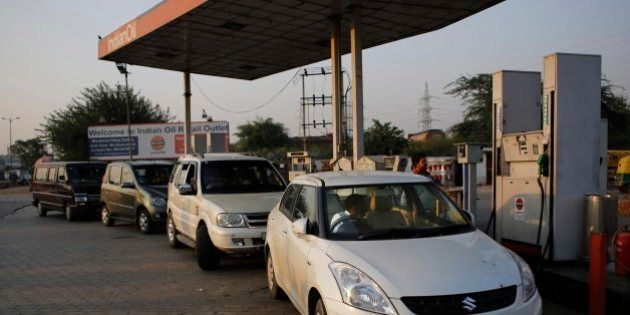 Vehicles are refueled at a petrol station in New Delhi, India, Thursday, Oct. 16, 2014. A sudden plunge...