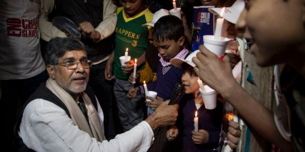 Indian children's rights activist Kailash Satyarthi holds a microphone for a child to speak during a...