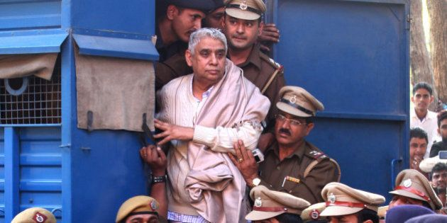 Controversial religious leader Sant Rampal stands by the door of a police van as he is brought to a court,...