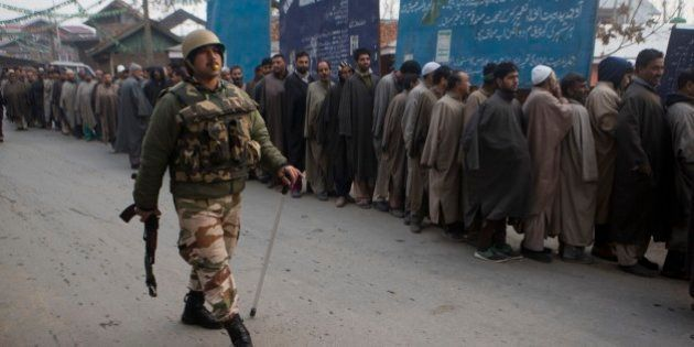 An Indian paramilitary soldiers walks past Kashmiri voters standing in queue outside a polling station...