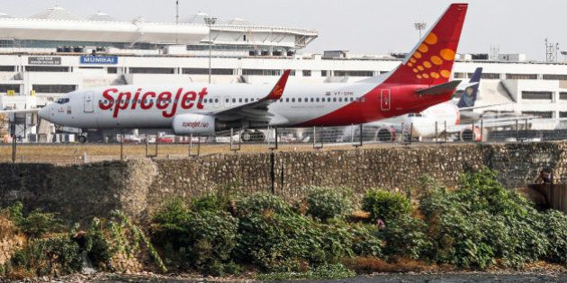 A SpiceJet Ltd. aircraft stands on the tarmac at Chhatrapati Shivaji International Airport in Mumbai,...
