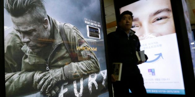 A man passes by a poster advertising Sony Pictures movie