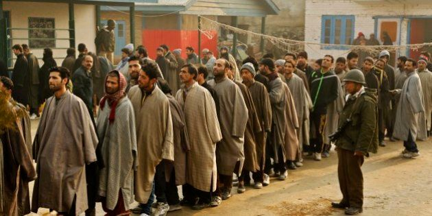 An Indian paramilitary soldier guards as Kashmiri men stand in queues to cast their votes during the...