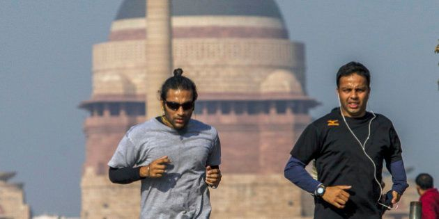 People jog along King's Way boulevard in front of the Presidential Residence in New Delhi, India, on...
