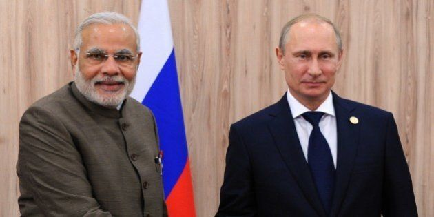 India's Prime Minister Narendra Modi (L) shakes hands with Russia's President Vladimir Putin during their...