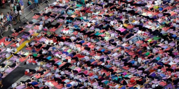 Thousands of New Yorkers are marking the first day of summer by practicing yoga in Times Square, during...