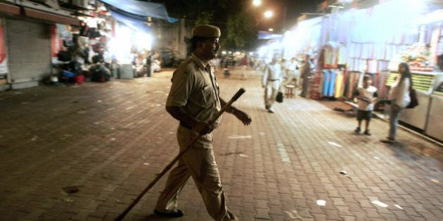 New Delhi, INDIA: A Delhi Policeman patrols a night market as the the Indian capital was put on a high...