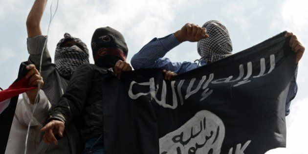 Kashmiri demonstrators hold up a flag of the Islamic State of Iraq and the Levant (ISIL) during a demonstration...