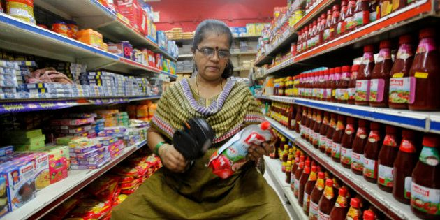 An Indian saleswoman puts a price tag on a product at a retail shop in Mumbai, India, Wednesday, Dec....