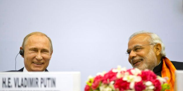 Indian Prime Minister Narendra Modi, right, and Russian President Vladimir Putin share a laugh as they...