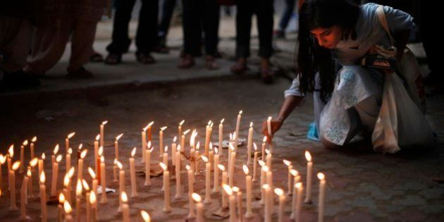 An activist places a candle on a pavement during a candle lit vigil to protest against the gang rape...