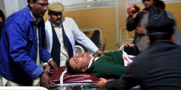 Hospital staff transport a student injured in the shootout at a school under attack by Taliban gunmen...