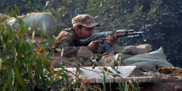 A Pakistani army soldier takes position on a bunker close to a school under attack by Taliban gunmen...