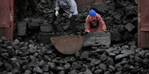 In this Nov. 27, 2014 photo, workers load coal from a truck to a process station in Tangxian in China's...