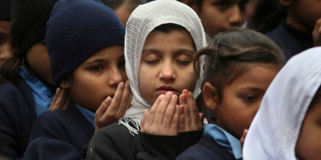 Pakistani students pray during a special ceremony for the victims of Tuesday's school attack in Peshawar,...