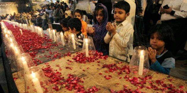 Pakistani children, chant prayers, during a candle light vigil for the victims of a Taliban attack on...