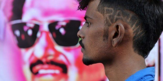 A young fan of Indian film actor Rajinikant, sporting the star's name in his hair-do, arrives at a movie...