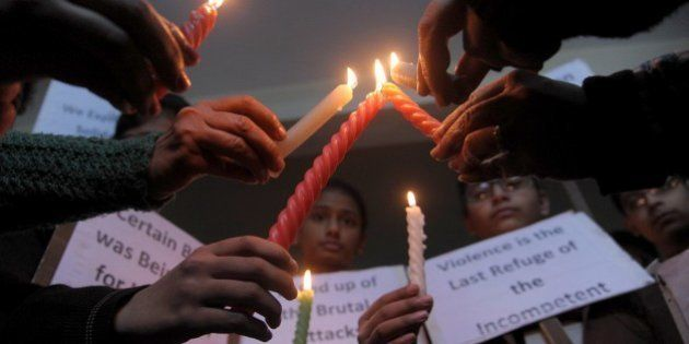 Indian schoolchildren hold placards and candles as they pay tribute to Pakistan children and staff killed...
