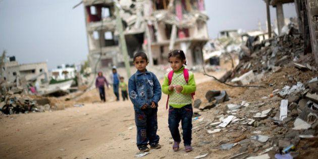 Palestinian school children walk through destroyed houses in Gaza City's Shijaiyah neighborhood, Sunday,...