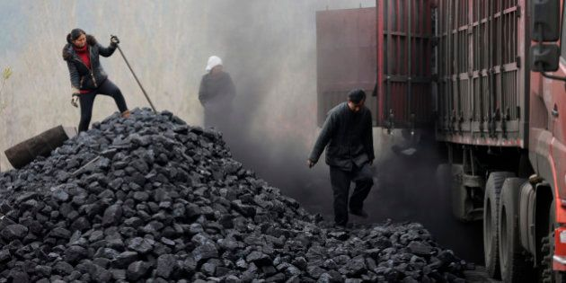 In this Nov. 27, 2014 photo, workers load coal from a truck at a process station for sale in Tangxian...