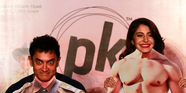 Bollywood actors Aamir Khan, left, and Anushka Sharma pose with movie character cut-outs during the teaser...
