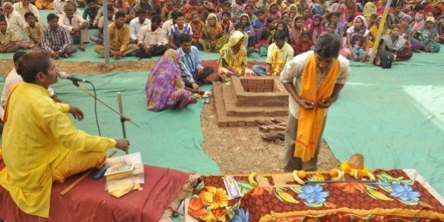 An Indian tribesperson (R, foreground) participates in a conversion ritual of some 200 Christians into...