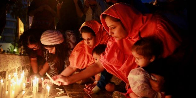 Indians lights candles during a prayer meeting in memory of the victims of Tuesday's Taliban attack in...