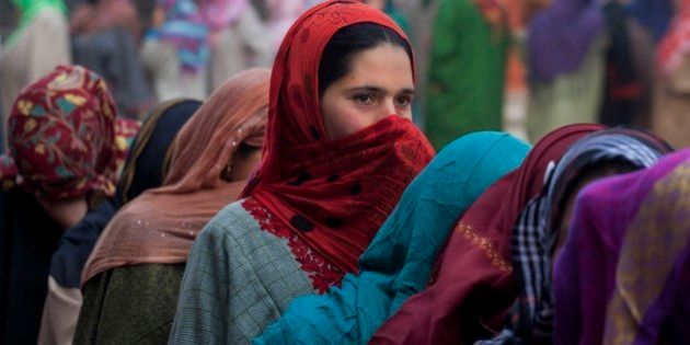 Kashmiri women stand in a queue to cast their votes during the fourth phase polling of the Jammu and...
