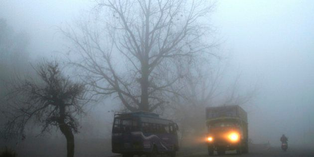 A truck passes amid morning fog on a national highway, near Jammu, India, Friday, Jan. 31, 2014. Dense...