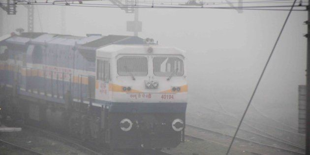 ALLAHABAD, INDIA - 2014/12/22: A train running slow during a cold and foggy morning. Train time departure...
