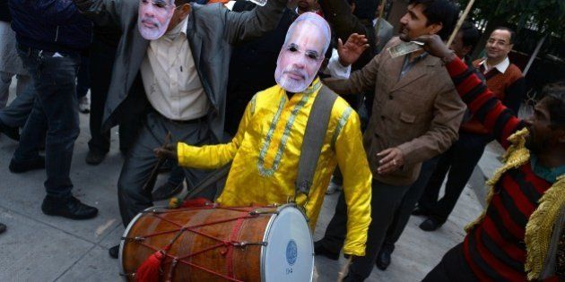 A traditional drummer wears a mask bearing the portrait of Indian Prime Minister Narendra Modi as Bharatiya...