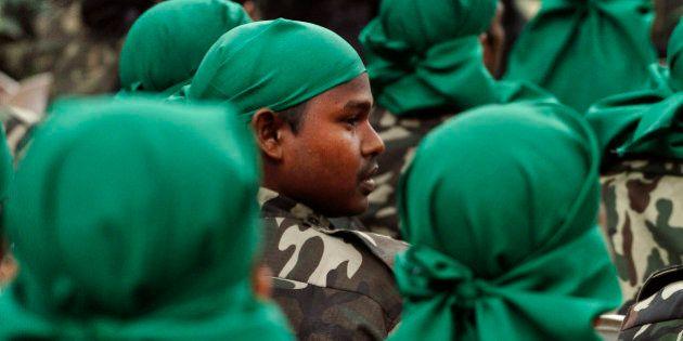 Militants of separatists group of Assam wait to surrender their weapons during a surrender ceremony in...
