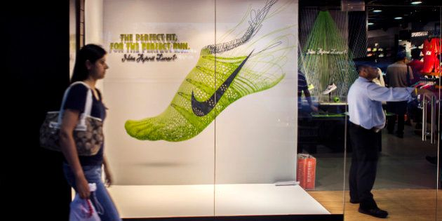 A pedestrian walks past a Nike Inc. advertisement in the window of a sports store at South Extension...