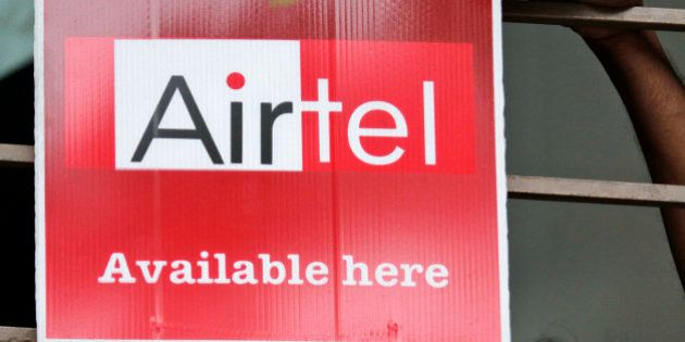A shopkeeper adjusts an Airtel board outside his shop in Calcutta, India, Wednesday, April 28, 2010....