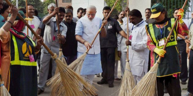 Indian Prime Minister Narendra Modi, center, sweeps an a road with a broom along with civic workers in...