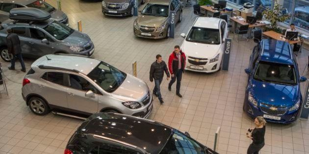 Customers examine cars on a display at an automobile dealership in Moscow, Russia, Saturday, Dec. 20,...