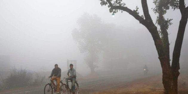 Indian villagers cycle amidst fog early morning in Allahabad, India, Friday, Dec. 5, 2014. Several parts...