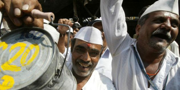 A lunch delivery man or 'Dabbawala' holds up a tiffin box as he participates in a session of 'Laughter'...