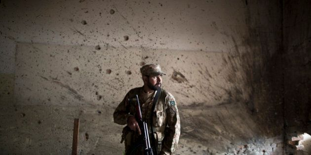 A Pakistani army officer stands in front of a wall riddled with bullet marks inside the Army Public School...