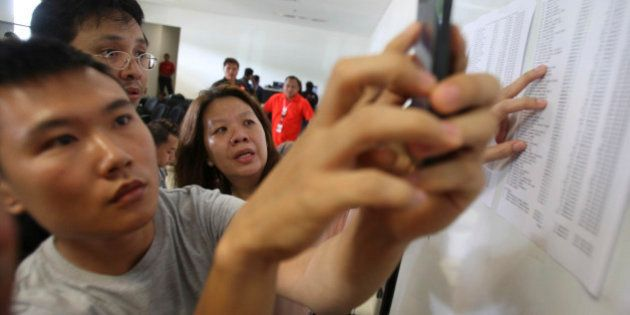 Relatives of the passengers onboard AirAsia flight QZ8501, check the plane's manifest at a crisis center...