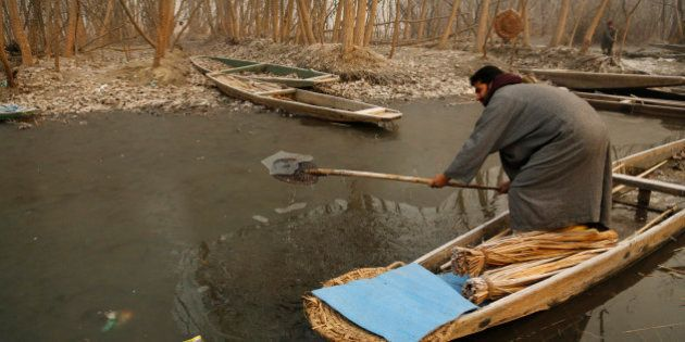 A Kashmiri boat man breaks the frozen surface of water of a Lake on a cold and foggy morning in Srinagar,...