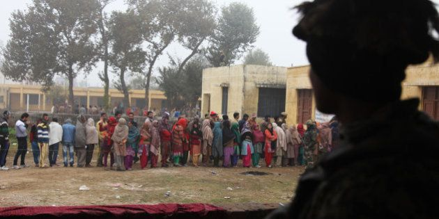 Indian paramilitary soldiers stand guard, as people stand in queues to cast their votes outside a polling...