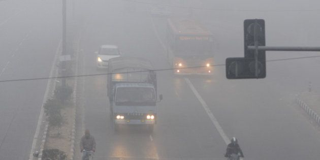 NEW DELHI, INDIA - DECEMBER 29: People commute amidst dense fog on a cold morning on December 29, 2014...