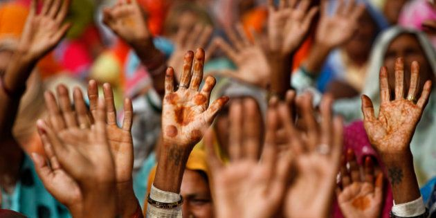 Women from rural northern India raise their hands during a protest in New Delhi, India, Thursday, Nov....