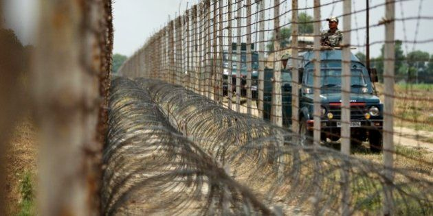 Indian Border Security Force soldiers patrol near the India-Pakistan international border fence during...