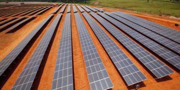 Technicians walk past solar panels at the government-run Fotovoltaica Solar Plant in Cobija, in the Amazon...