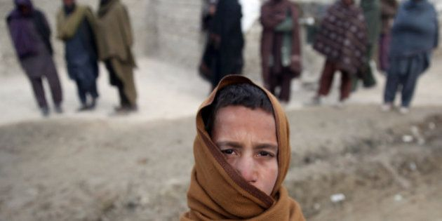 In this Wednesday, Dec. 24, 2014 photo, an internally displaced Afghan youth wraps himself against the...