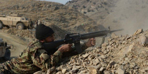 In this picture taken on January 3, 2015, an Afghan National Army (ANA) soldier fires during an ongoing...