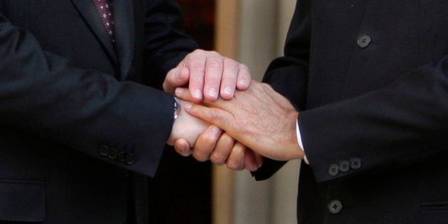 Indian Prime Minister Manmohan Singh, his hands seen on right, shakes hands with Russian Prime Minister...